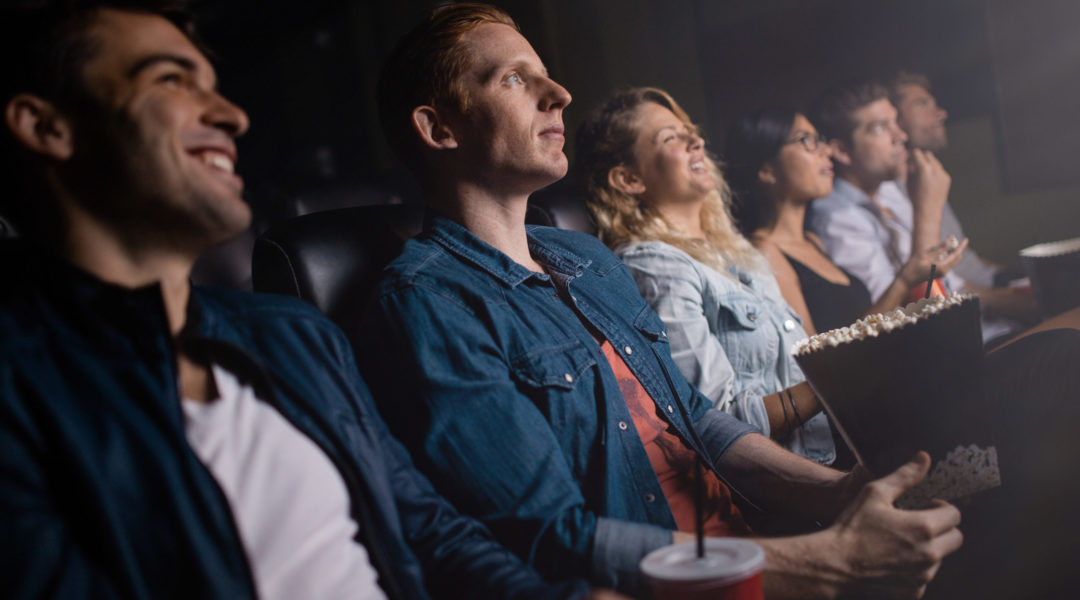 Group of people in theater watching movie. Young man with friends in cinema.