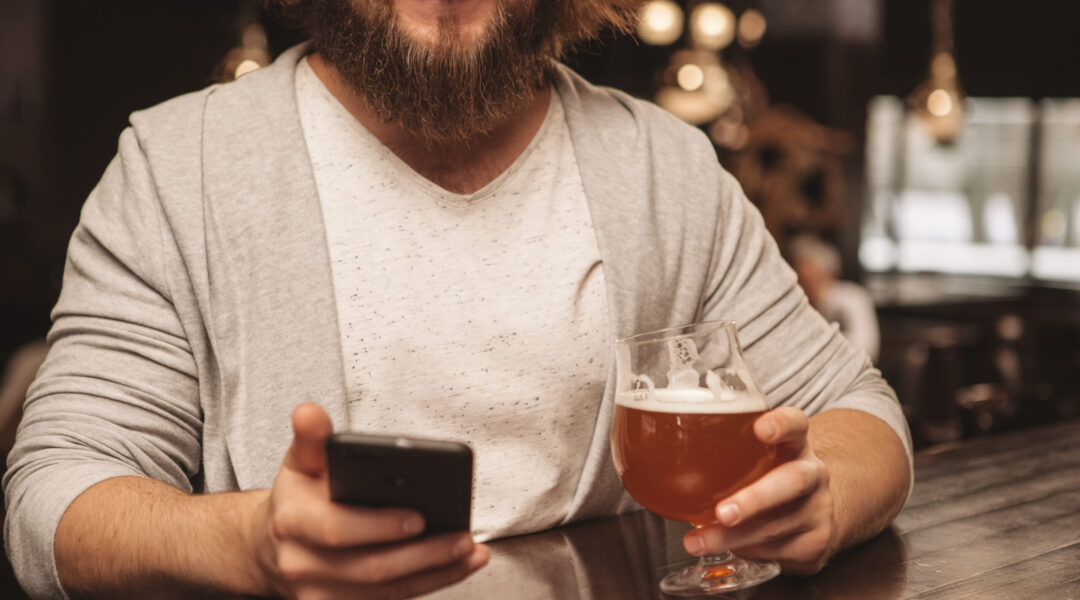 Cropped,Shot,Of,A,Bearded,Man,Smiling,,Using,His,Smart